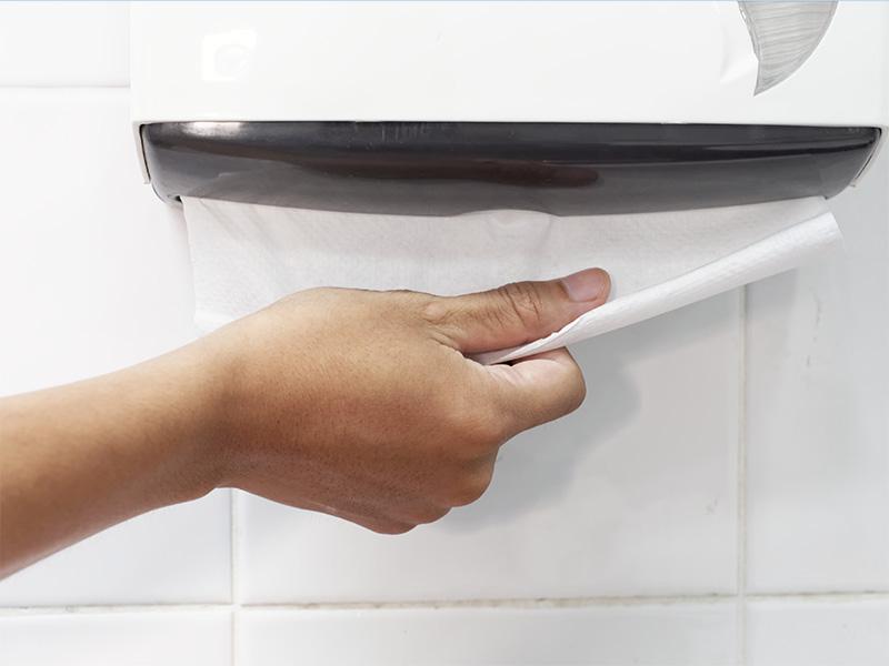 Mann trocknet sich die die Hände mit einem Papierhandtuch